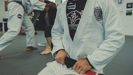 person-wearing-a-gi-on-knees-during-brazilian-jiu-jitsu-class